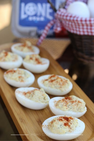 simple deviled eggs on a brown platter with eggs in the background