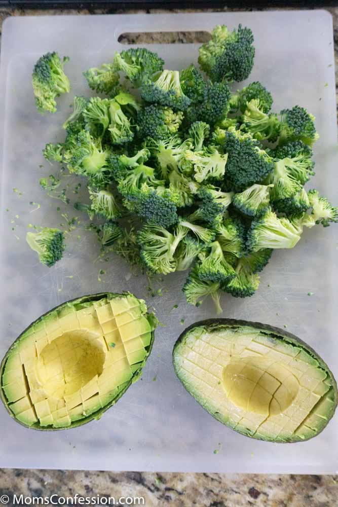 Chopped broccoli and avocado on a cutting board