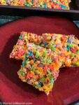 Fruity Pebble Rice Crispy Treats cut into squares on a red plate